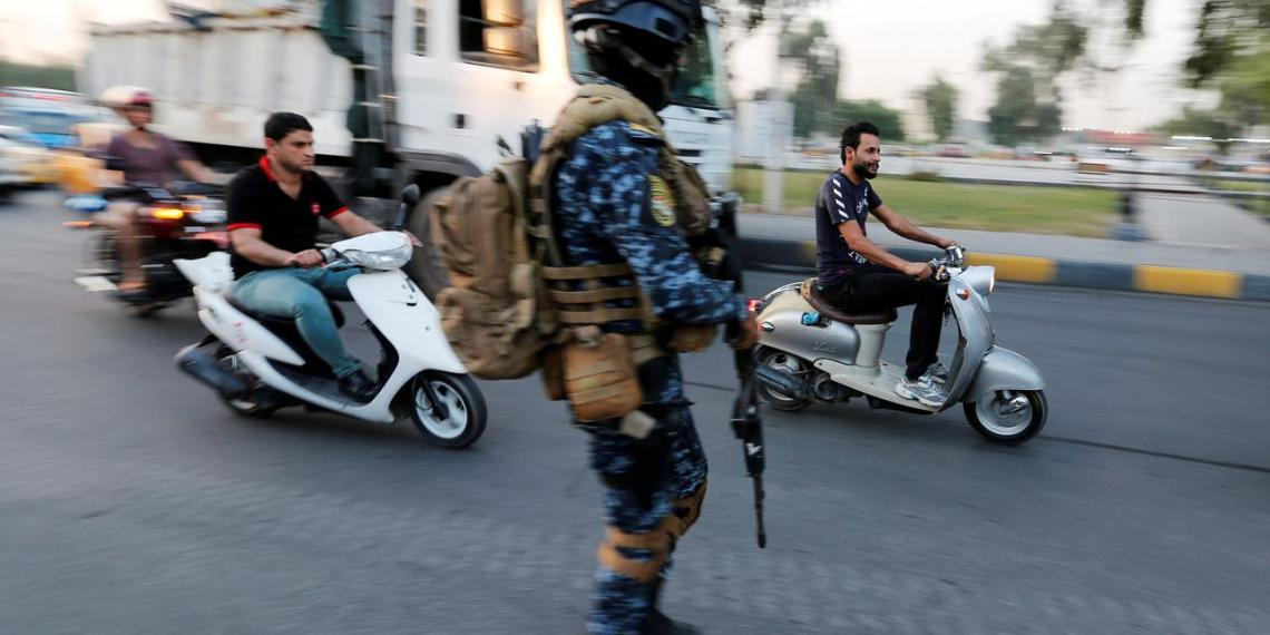 FILE PHOTO: Men ride motorbikes past a member of Iraqi federal police in a street in Baghdad, Iraq October 7, 2019. REUTERS/Wissm al-Okili