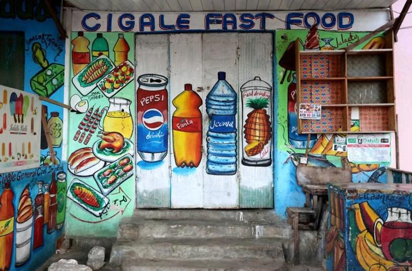 Baixas taxas de alfabetização na Somália significa que as pessoas têm que 22ver22 o que compram para que as vitrines tenham murais incríveis  - Você Sabia? Vitrines na Somália tem que ter desenhos