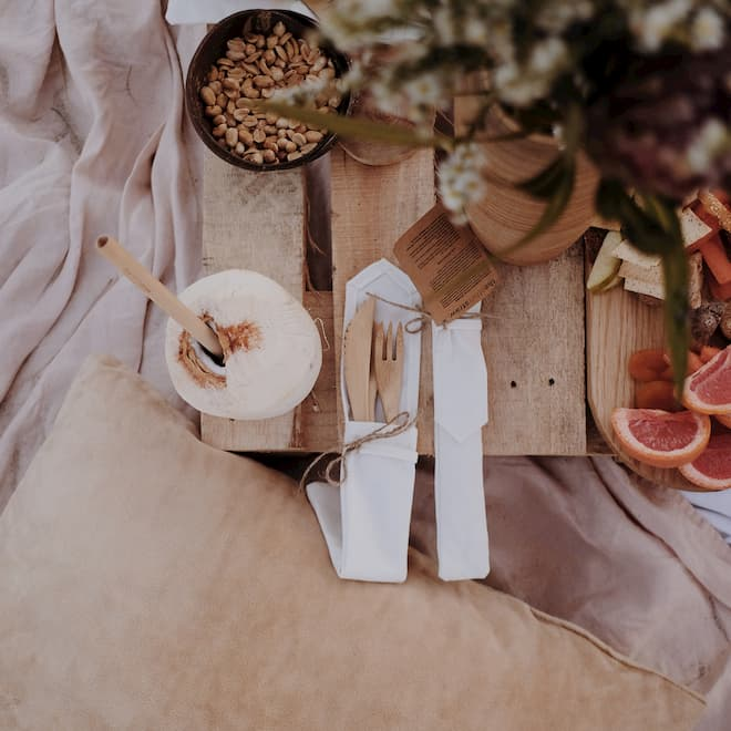 bamboo cutlery on a table with food and bamboo straws