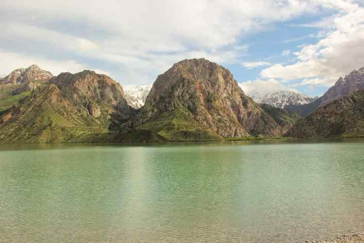 Stunning mountains surrounding the emerald green Iskanderkul Lake in Tajikistan