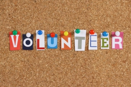 the word volunteer in cut out magazine letters pinned to a cork notice board