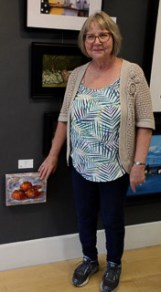 woman standing by small painting of fruit