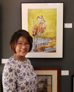 Woman standing next to watercolor painting of Sandhill Cranes.