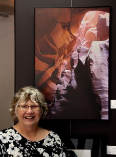 Woman standing under a large photo of part of the Grand Canyon.