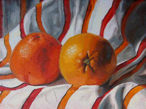 Oranges laying on a white towel with red and orange stripes.