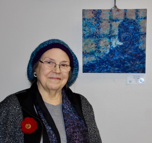 Woman standing next to blue painting.