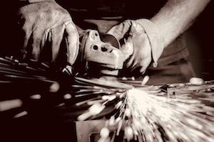 Gloved hands using grinder