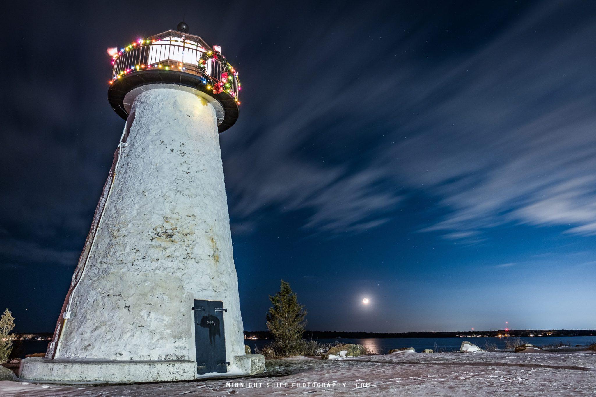 A Waxing Crescent Moon can be seen behind Neds Lighthouse in Mattapoisett, Massachusetts