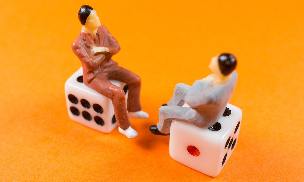 サイコロに座って向き合うミニチュアの人