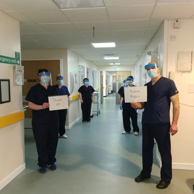 5 nurses standing in a hospital ward with the sign thank you Midton in their hands