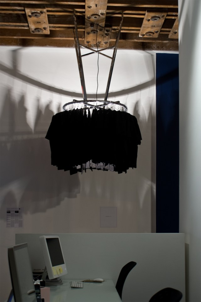 Untitled, 2009. Chrome clothing rack, chrome hangers, black t-shirts, light bulb. Dimensions variable.