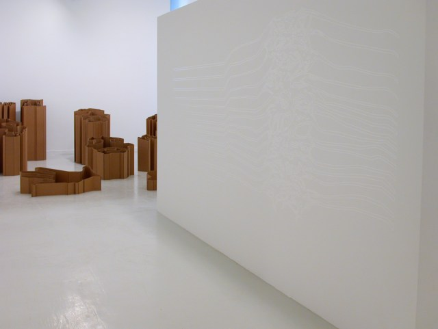 """Jay Heikes and Kirk McCall, installation view. Left: Kirk McCall, Queen II, 2002. 2-ply cardboard. Dimensions variable. Right: Jay Heikes, The Joy Division, 2001. Vinyl. 52"""" x 124"""". Edition of 1."""