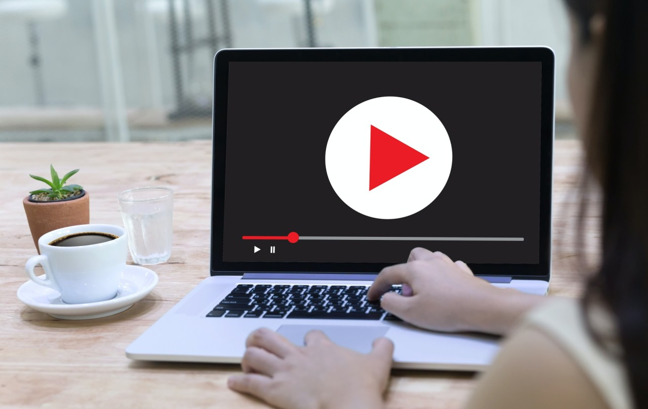 Woman clicking play on her laptop to start a video ad