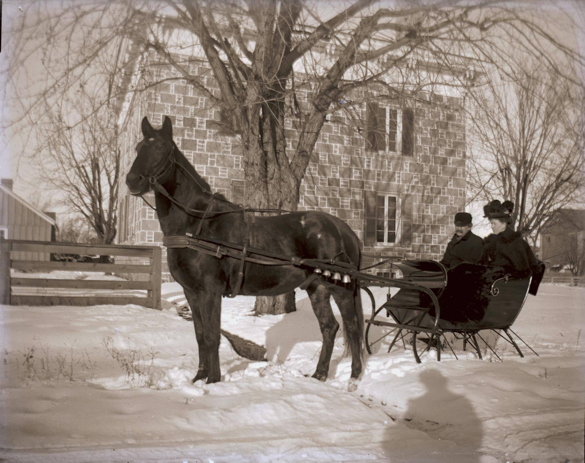 Sleigh ride in front of a stone house make with 'block and stack' technique.
