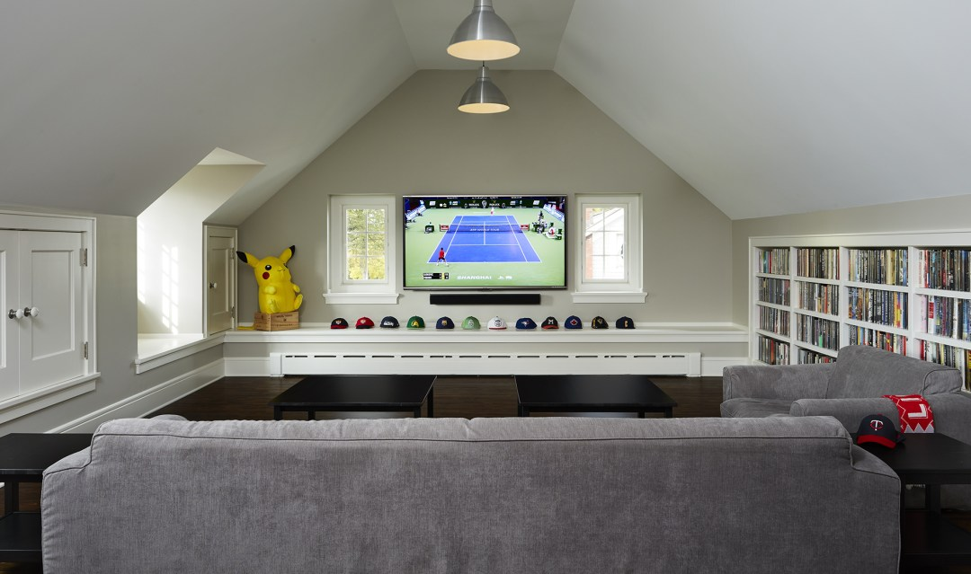 Room with tv and row of hats displayed