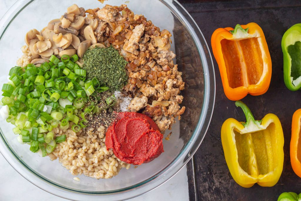Bowl filled with ingredients next to a plate of bell peppers cut in half