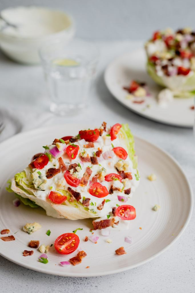 A straight on picture of a serving of iceberg wedge salad on a white plate.