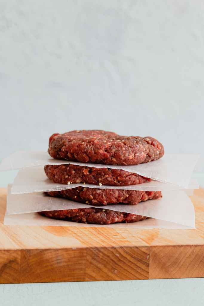 Raw ground venison portioned out into burger patties are stacked between pieces of wax paper on a cutting board.