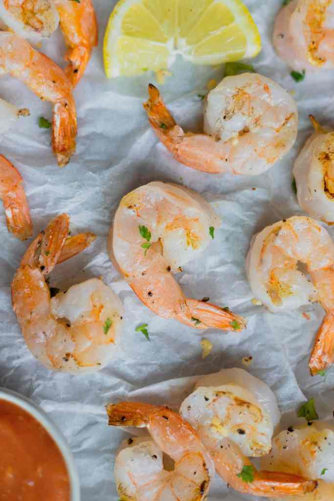 Grilled shrimp on a piece of parchment paper sprinkled with fresh parlsey.