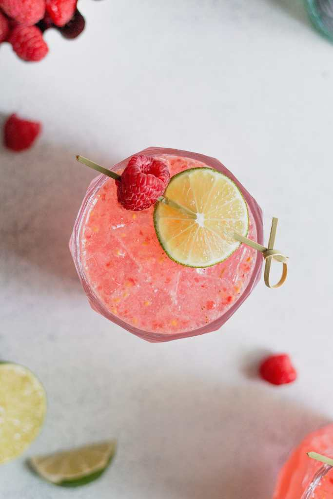 An overhead shot of a raspberry gin fizz without egg whites in a rocks glass. The drink is garnishes with a circular lime slice and raspberry.