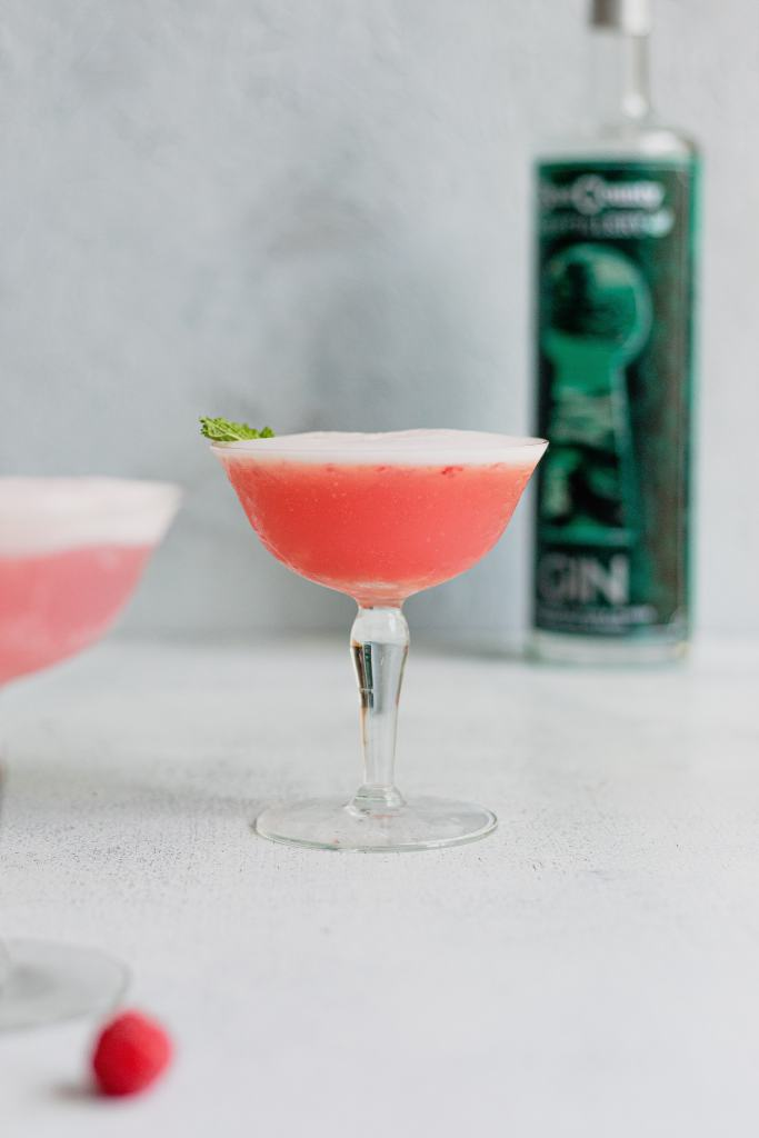 A bright pink drink in a vintage coupe glass with a green bottle of gin behind it on a grey background.