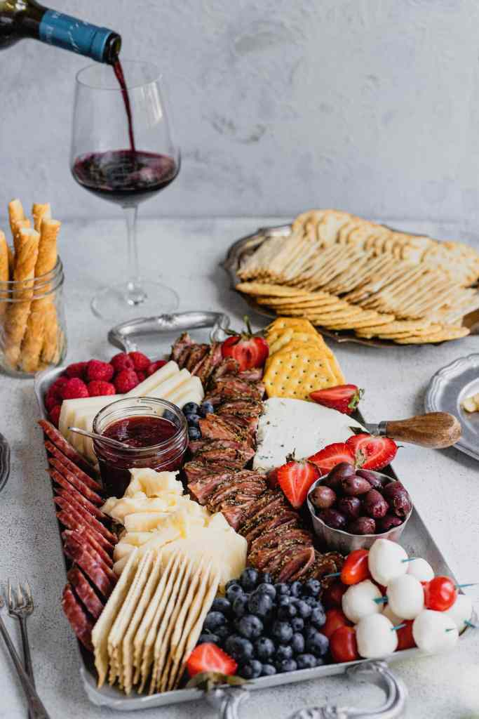 An antqiue silver tray laden with cheese, meat, and fresh fruit in colors of red, white, and blue to celebrate Fourth of July. A hand pours a glass of red wine in the background.