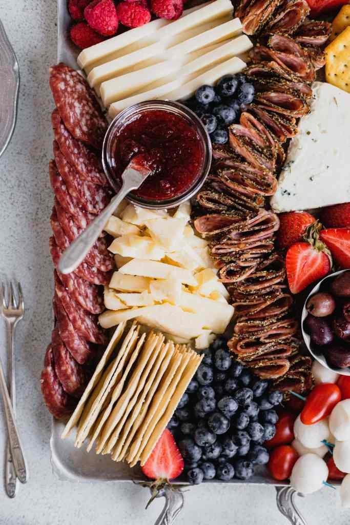 Aged white cheddar cheese sits on a silver tray surrounded by salami, crackers, fruits, and jam in this patriotic cheese tray.