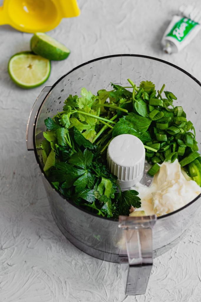 Bright green herbs, sour cream, and mayo are in the bowl of a food processor sitting on a grey backdrop.