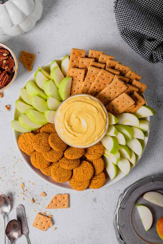 An overhead shot of a small bowl of pumpkin pie cheesecake dip surrounded by gingersnaps, graham crackers, and apple wedges. Everything sits on a white backdrop.