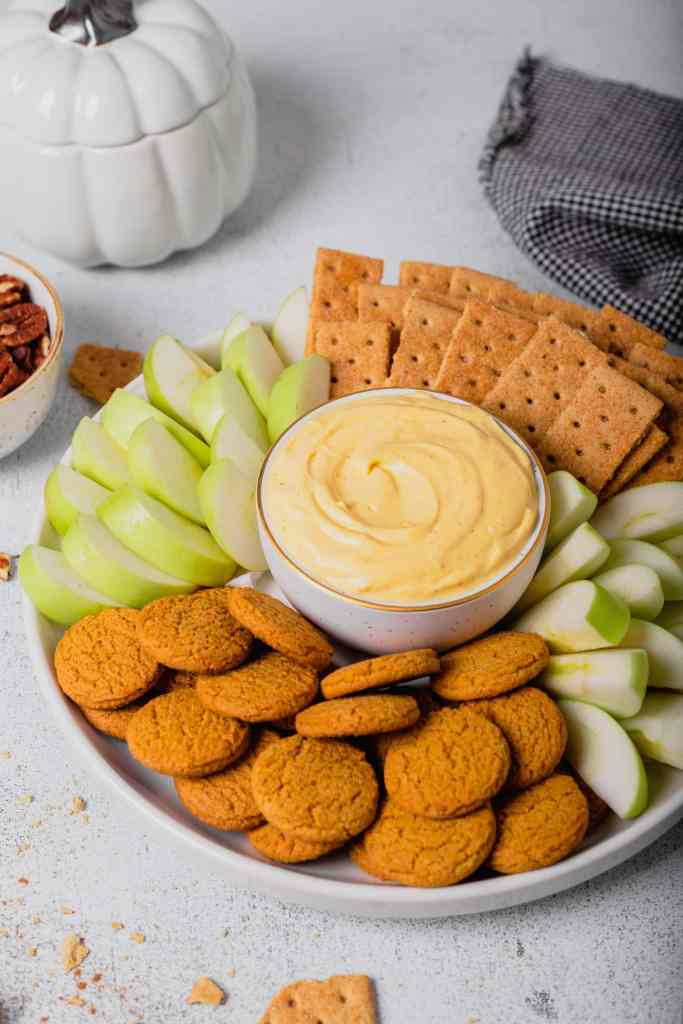 A white tray holds graham crackers, gingersnap cookies, and green apple slices. They surround a small white bowl full of pumpkin pie cheesecake dip.