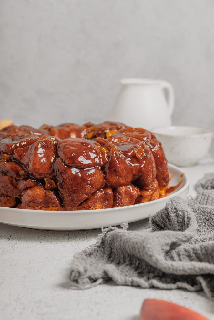 A white plate is full of fresh baked monkey bread. There is a white linen next to the plate and a white bowl and pitcher in the background. Everything sits on a light grey backdrop.