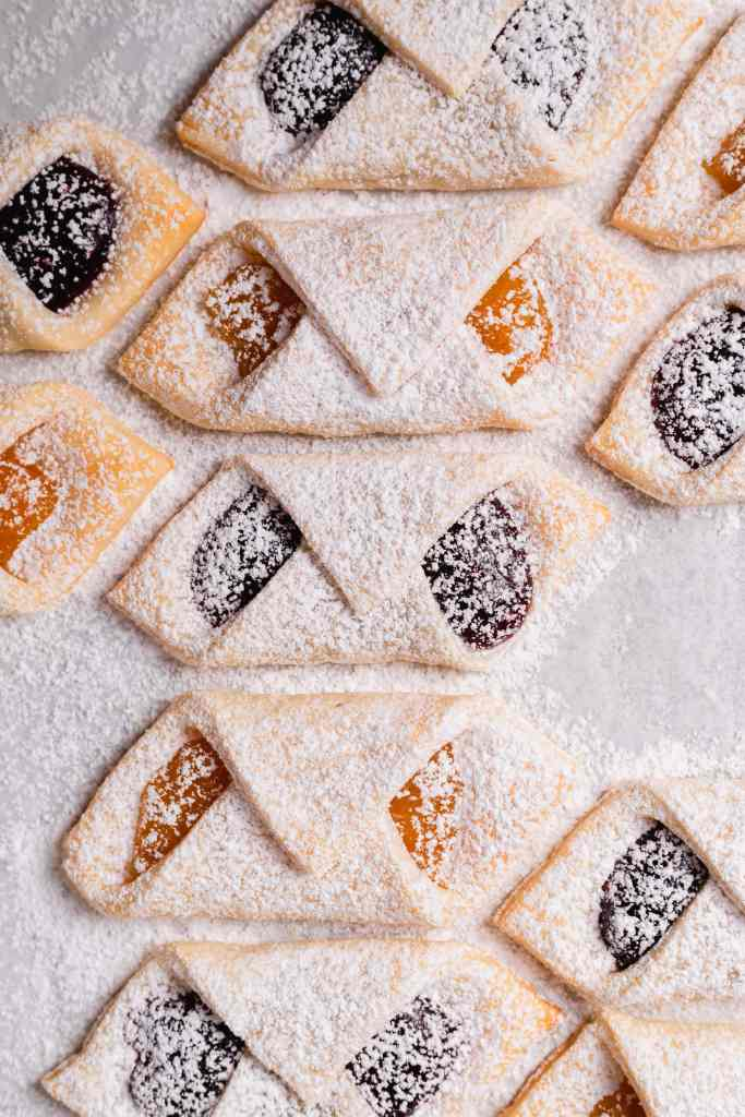 An overhead shot of apricot and raspberry Kolaczki (polish cream cheese cookies) on a piece of white parchment paper.