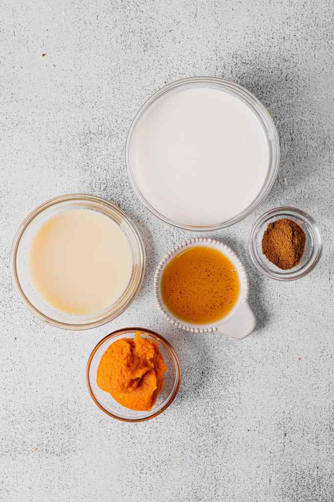 A flatlay of different sized glass bowls filled with the ingredients for pumpkin cream cold foam. These include: heavy whipping cream, sweetened condensed milk, vanilla extract, pumpkin puree, and pumpkin pie spice.