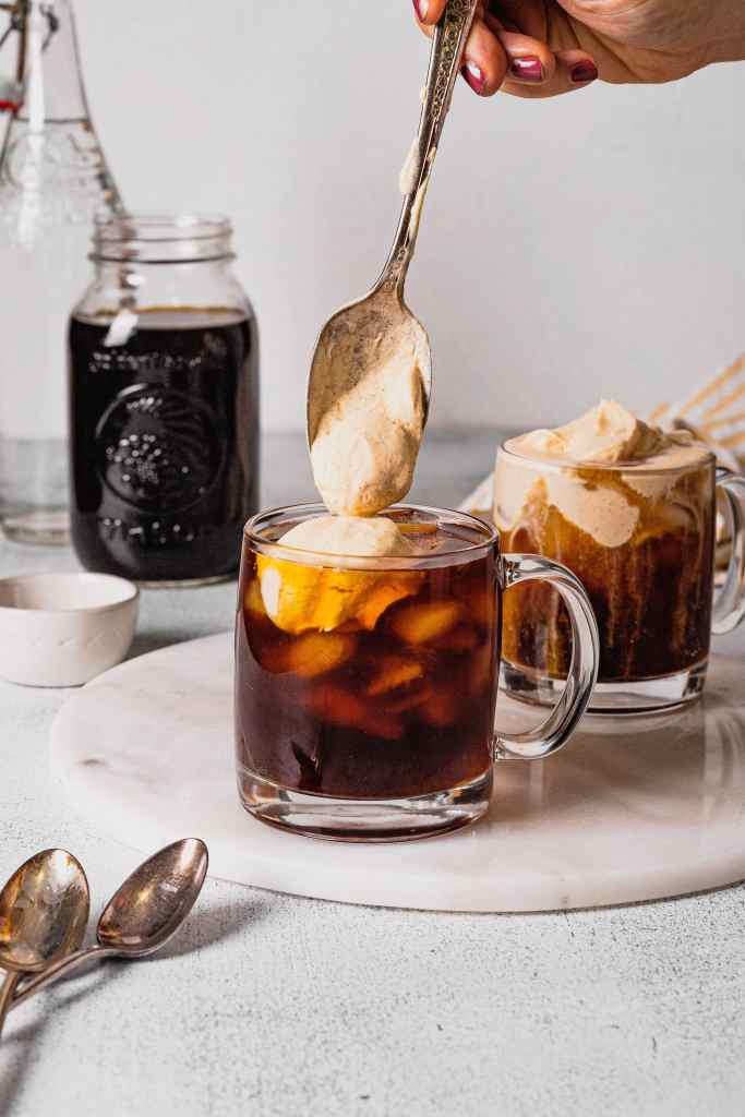 A hand holds an antique silver spoon filled with pumpkin cream cold foam and tops a glass of cold brew coffee with it.
