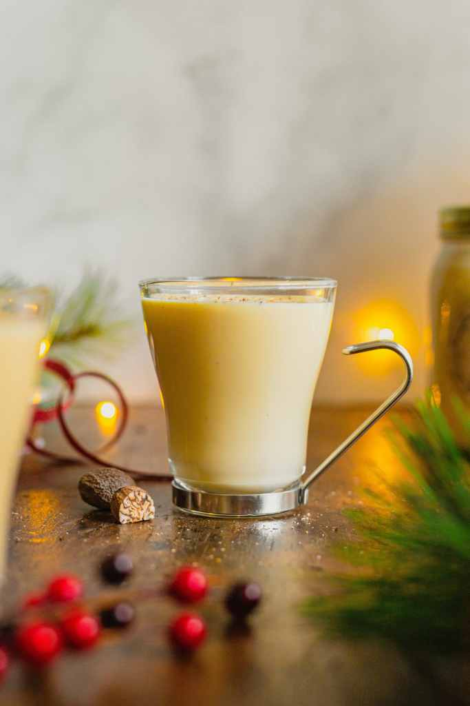 A clear glass with a metal handle is filled with homemade boozy eggnog and topped with a sprinkle of freshly ground nutmeg. The glass is on a wooden tabletop with other holiday decor and glasses of eggnog.