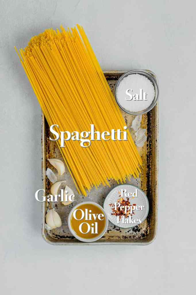All of the ingredients for a recipe of spaghetti aglio e olio are arranged on a metal baking tray.