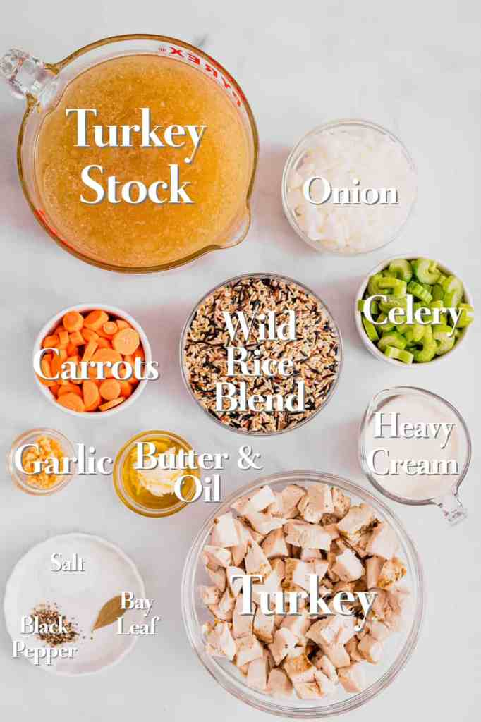 All of the ingredients for creamy turkey and rice soup are in various glass bowls and measuring cups on a white backdrop.