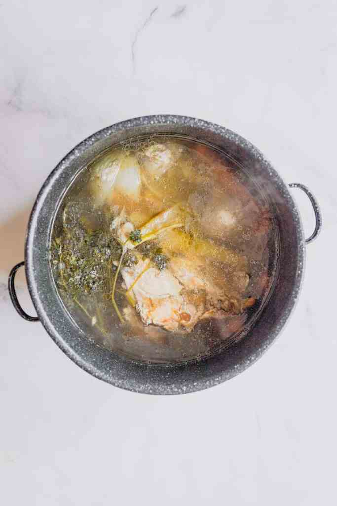 Turkey stock after it has been simmered for a few hours in a large stock pot.