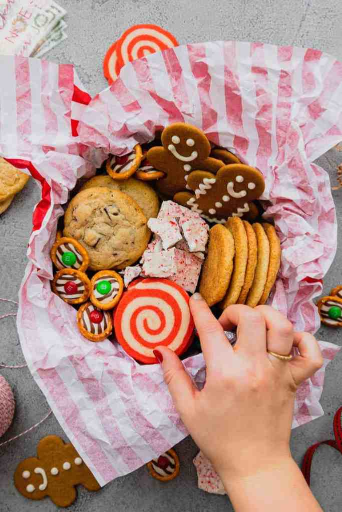 A cookie tin full of Christmas cookies and treats lined with red and white striped tissue paper.