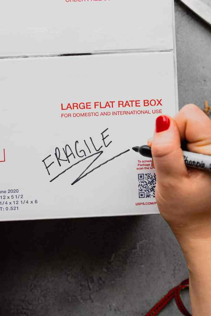 "The word ""FRAGILE"" is written on a USPS shipping box in permanent marker."