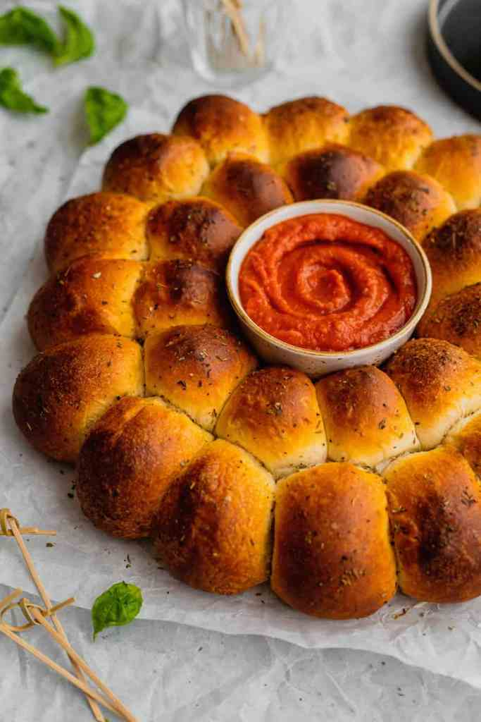 A Christmas wreath pull apart bread appetizer stuffed with mozzarella cheese and pesto sits on parchment paper with a small bowl of marinara sauce in the center.