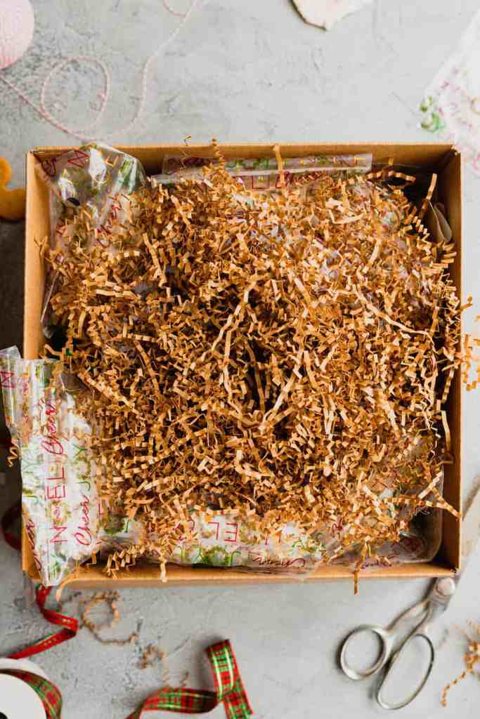 Brown shredded paper is set on top of the whole package before the box is sealed shut.