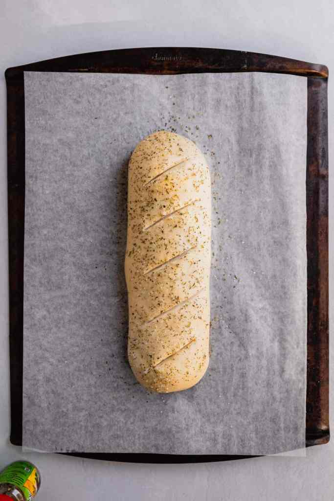 A loaf of unbaked bread brushed with butter and sprinkled with herbs on a parchment lined baking sheet.