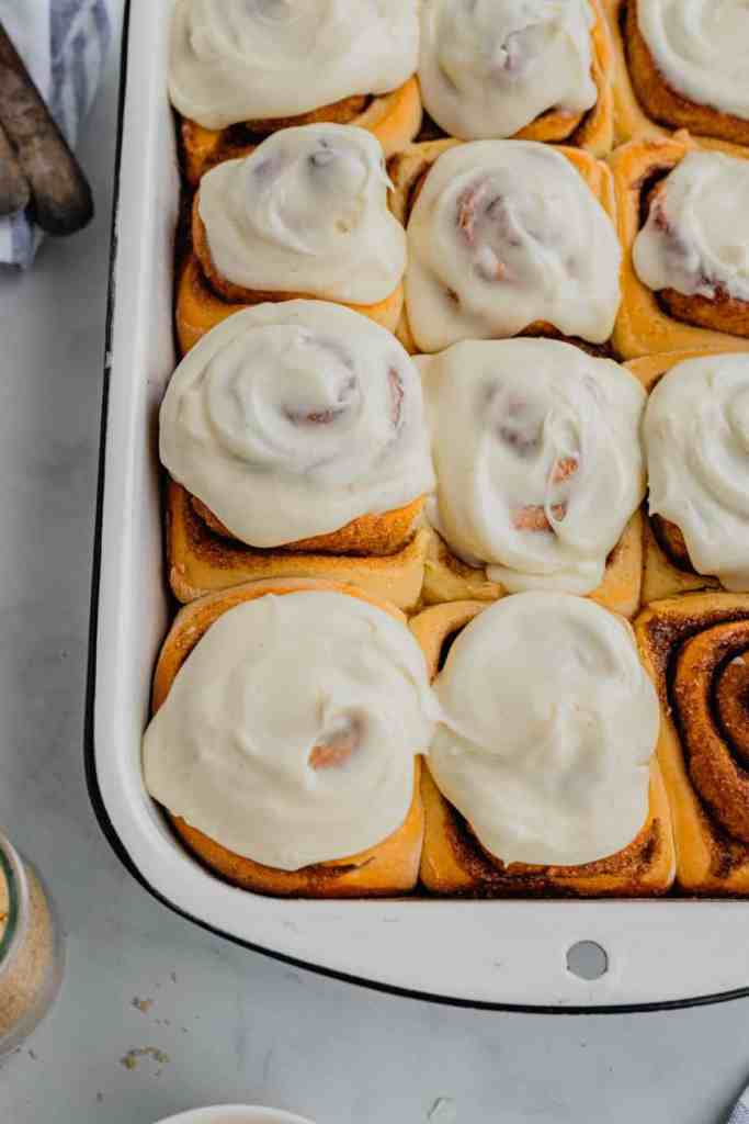 A white enamel pan is filled with a batch of overnight cinnamon rolls recipe covered in cream cheese frosting.