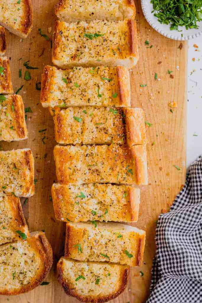 An overhead shot of freshly baked homemade garlic bread on a wooden cutting board.