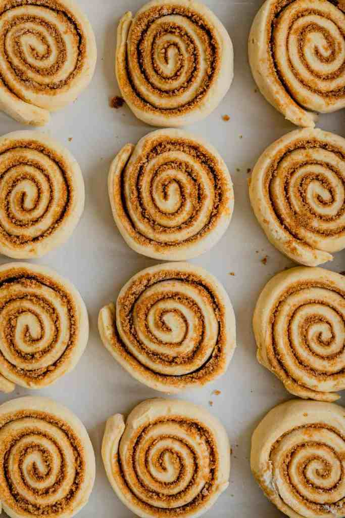 Unbaked cinnamon rolls are lined up in a white baking dish.
