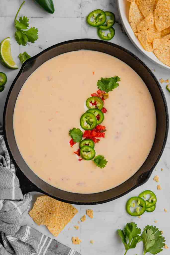 A cast iron skillet is filled with homemade queso dip. It is garnished with tomatoes, chilies, and cilantro.