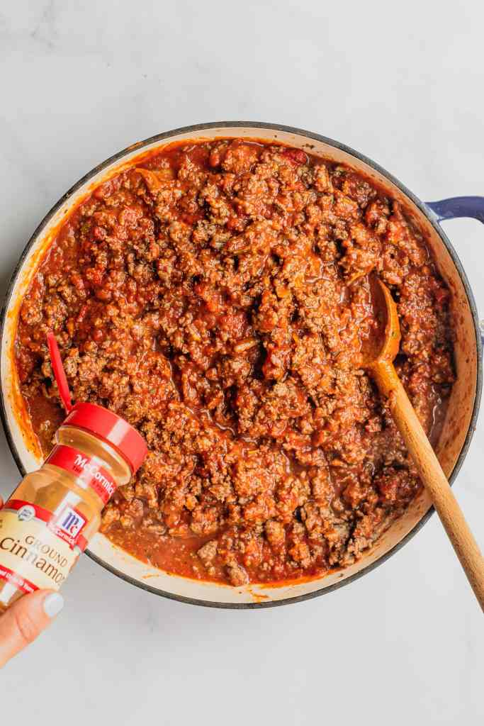 Cinnamon is added to a meat sauce for a homemade lasagna recipe.