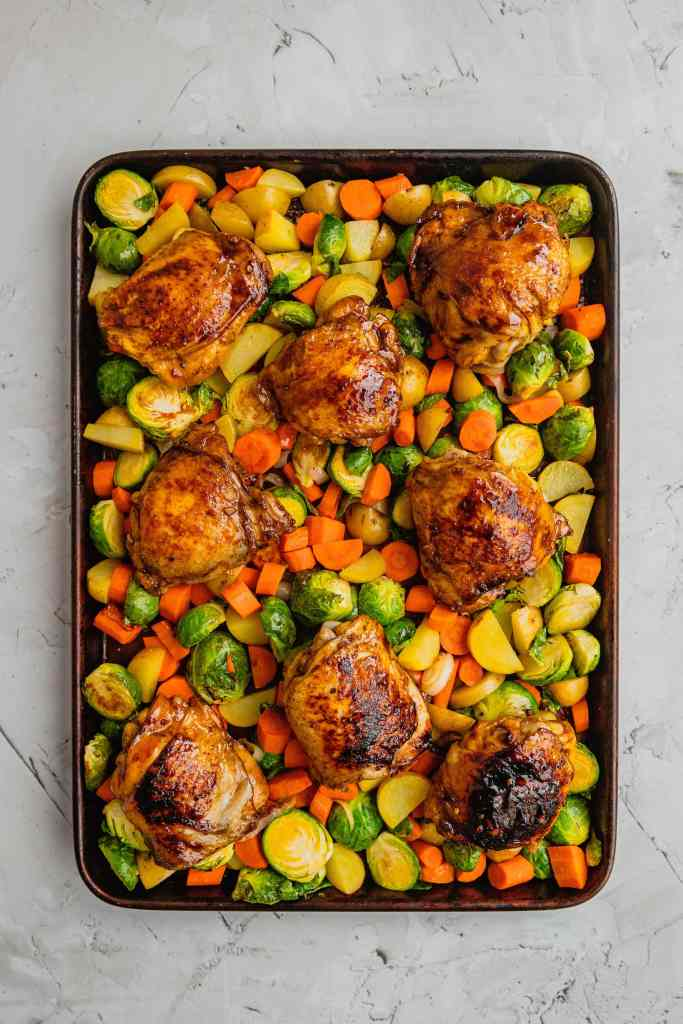 A sheet pan filled with vegetables and honey balsamic chicken thighs.