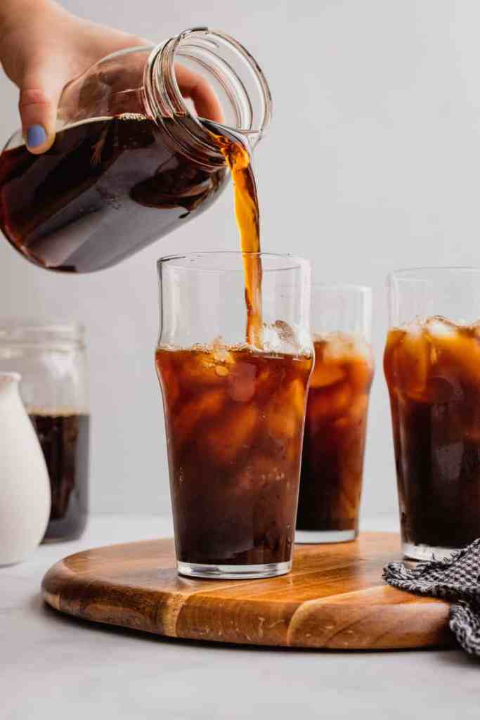 Homemade cold brew coffee gets poured into a glass filled with ice.